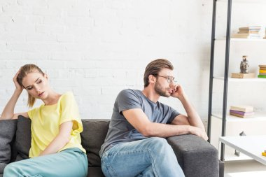 upset young couple sitting separated on sofa at home