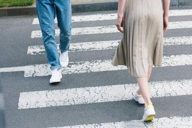 cropped image of stylish man in jeans and woman in long skirt walking on crosswalk
