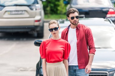 stylish young couple of models in sunglasses posing near car