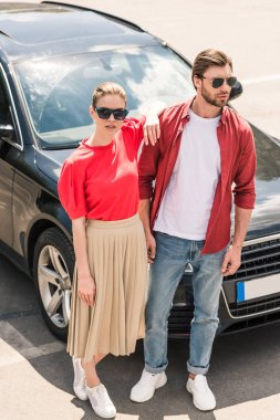 stylish couple of models in sunglasses posing near black car