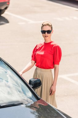 high angle view of stylish young female model in sunglasses opening door of car