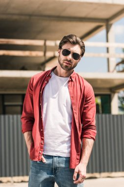 portrait of young stylish man in sunglasses posing in front of construction building