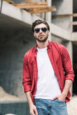 young stylish man in sunglasses at construction building