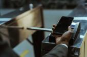 Fotografie Nahaufnahme der Geschäftsmann ÖPNV-Tarif mit dem Smartphone bezahlen
