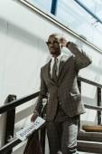 Fotografie Stylový jistý podnikatel s novinami, chůze po schodech