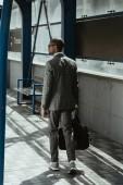 Fotografie Zuversichtlich Geschäftsmann zu Fuß auf öffentliche Packstation