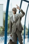 Fotografie Young african american businessman waving to someone on train station
