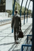 Fotografie Businessman in stylish suit walking on public transport station