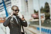 Fotografie Afrikanische amerikanische Geschäftsmann Anzug mit Smartphone und Kaffee Tasse Zug warten