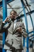 Young african american businessman talking on smartphone on transport station