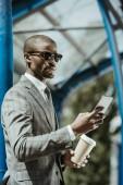 Fotografie Stilvolle zuversichtlich Geschäftsmann mit Smartphone und Kaffee Tasse Zug warten