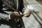 Fotografia Vista potata di uomo daffari afroamericano vestito con smartphone e tazza di caffè