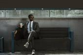 Fotografie Stylový jistý podnikatel s šálek kávy sedí na lavičce vlakové nádraží