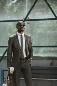 Fotografie Stilvolle zuversichtlich Geschäftsmann mit Aktenkoffer und Kaffee Tasse stehen auf ÖV-station