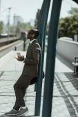Fotografie Stilvolle zuversichtlich Geschäftsmann Musikhören und Bahnhof Kaffeetasse festhalten