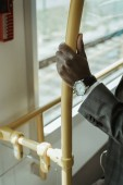 Fotografie Cropped view of african american businessman wearing watch while taking train