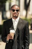 Stylový podnikatel na sobě bílou košili a sako, poslouchá hudbu a drží šálek kávy