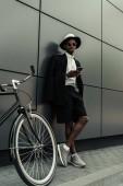 Stylový muž na sobě bílou košili a sako pomocí smartphone stoje na jeho kole
