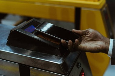 Cropped view of male hand with smartphone paying public transport fare