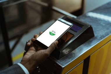 Close-up view of businessman using Google Pay paying for public transport