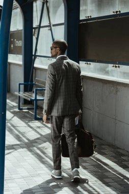 Confident businessman walking on public transport station