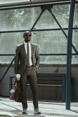 African american businessman wearing suit with briefcase and coffee cup standing on public transport station