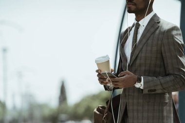 Cropped view of African american businessman wearing suit listening to music and holding coffee cup on train station