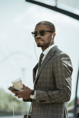 Young african american businessman listening to music and holding coffee cup on public transport station