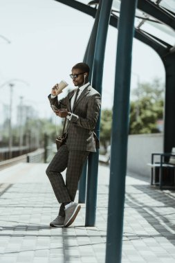 Smiling confident businessman listening to music and holding coffee cup on public transport station