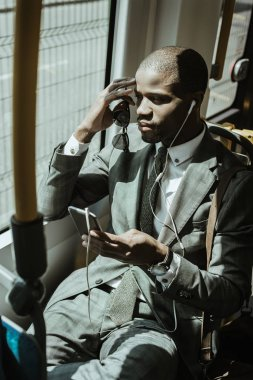 African american businessman wearing suit listening to music while going to work by train
