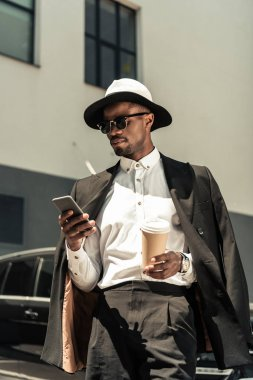 Handsome young african american businessman listening to music and holding coffee cup