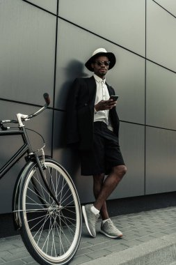 Stylish man wearing white shirt and jacket using smartphone while standing by his bicycle
