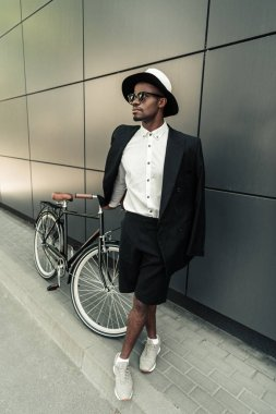 Fashionable african american man wearing fedora hat standing by his bicycle