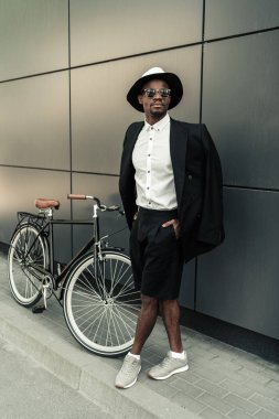 Handsome young african american man posing by his bicycle