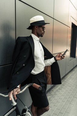 Fashionable african american man wearing fedora hat using smartphone while holding his bicycle