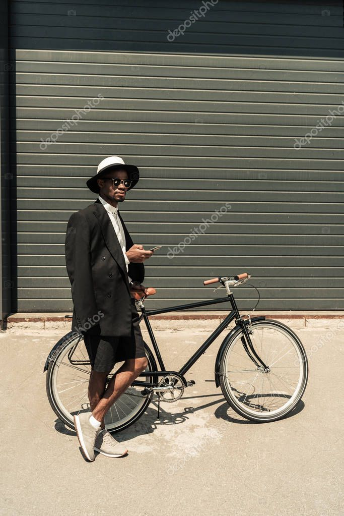 Stylish man wearing white shirt and jacket using smartphone while holding his bicycle
