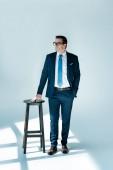 Fotografie Ganzkörperansicht eines ernsthaften Geschäftsmannes mit Brille, der in der Nähe von Hockern steht und wegschaut