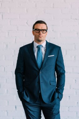 confident middle aged businessman in suit and eyeglasses standing with hands in pockets and looking at camera