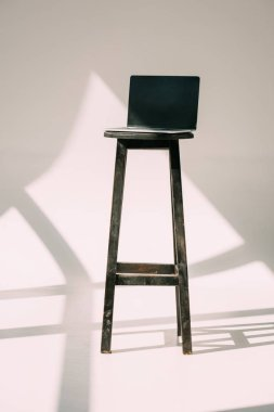 laptop with blank screen on wooden stool on grey