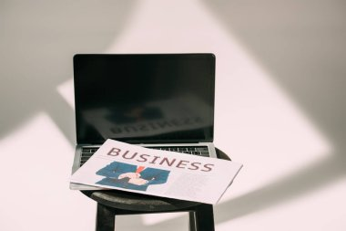 close-up view of laptop with blank screen and business newspaper on stool on grey
