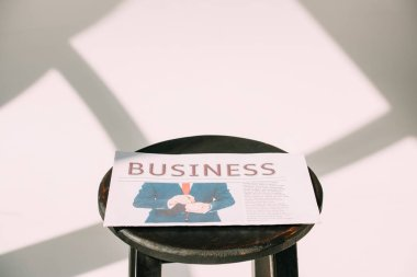 close-up view of business newspaper on wooden stool on white