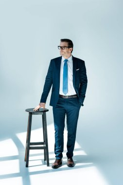 full length view of serious buisnessman in eyeglasses standing near stool and looking away on white