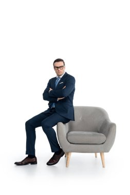 full length view of confident businessman in eyeglasses sitting with crossed arms and looking at camera on white