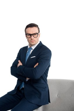 confident businessman in eyeglasses sitting with crossed arms and looking at camera isolated on white