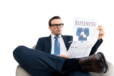 confident middle aged businessman in eyeglasses sitting in armchair and reading newspaper isolated on white