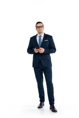 full length view of confident buisnessman in eyeglasses holding smartphone and looking at camera isolated on white