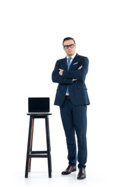 confident businessman standing with crossed arms near laptop on stool on white
