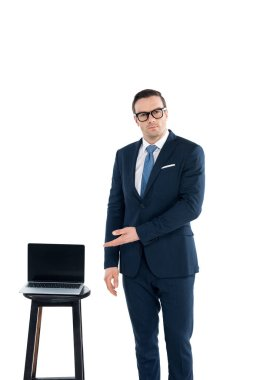 middle aged buisnessman in eyeglasses pointing at laptop with blank screen and looking at camera isolated on white