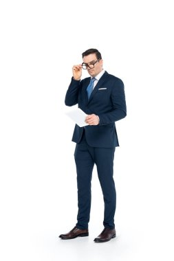 full length view of businessman in eyeglasses holding digital tablet and looking at camera isolated on white