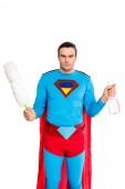 Fotografie man in superhero costume holding duster and spray bottle isolated on white